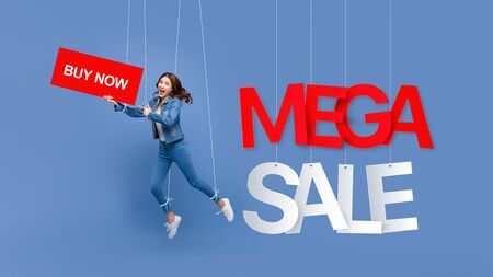 Excited beautiful Asian woman puppet on strings holding BUY NOW sign with MEGA SALE texts hanging on light blue background 版權商用圖片 - 146352728