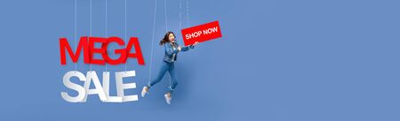 Excited beautiful Asian woman puppet on strings holding BUY NOW sign with MEGA SALE texts hanging on light blue banner background with copy space 版權商用圖片