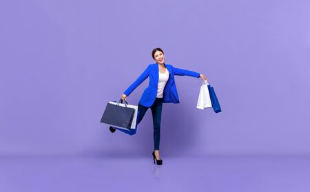 Smiling beautiful young Asian woman in white blue clothes holding shopping bags standing in purple background 版權商用圖片 - 146353378