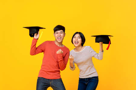 Excited happy Asian college students holding graduate caps in colorful yellow studio background
