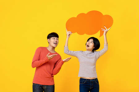 Young Asian college student friends in casual clothes with speech bubble on colorful yellow studio background 版權商用圖片