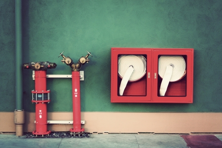 fire fighting equipment: Vintage Hydrant with water hoses and fire extinguish equipment Stock Photo