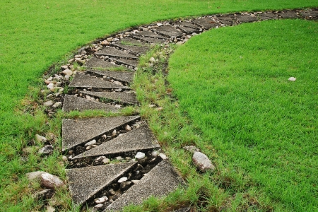 Stone path through a green grassy lawn photo
