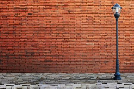 lamp post: Lampione stradale sul muro di mattoni di sfondo Archivio Fotografico