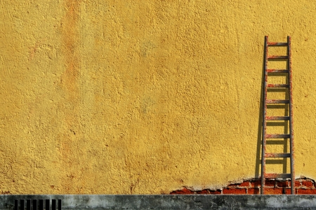 Old ladders on blank yellow wall