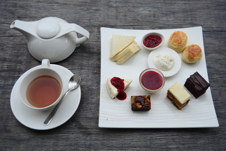 Traditional afternoon tea set on wooden table photo