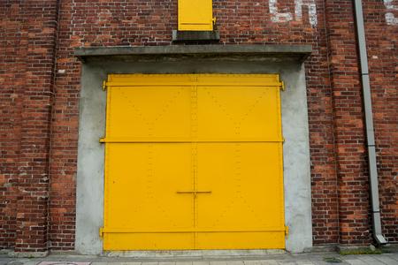 porte jaune dans un mur de briques rouges