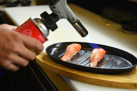 Chef using a torch burn on salmon - Salmon Saikyo sushi