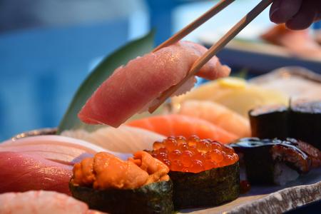 Bacchette che prendono un pezzo di Otoro da Sushi Set nigiri e rotoli di sushi che servono con salsa di soia, cucina famosa del Giappone Archivio Fotografico
