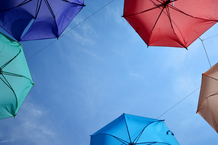 Vibrant colorful opened umbrellas background. Colorful umbrellas in the sky for wallpaper, summer