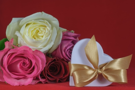 heart shaped gift box with rose on red background photo