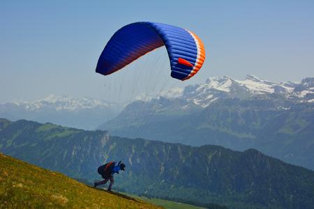 high flier: Paraglider prepareing to take off from a mountain Niederhorn Switzerland