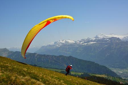 Paraglider prepareing to take off from a mountain Niederhorn Switzerland photo