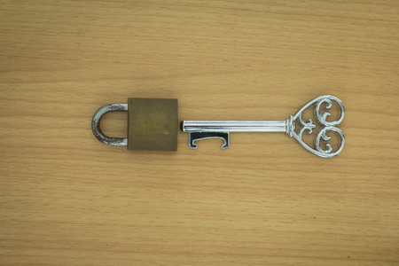 door lock love: Key with a heart inside and lock on wood background Stock Photo