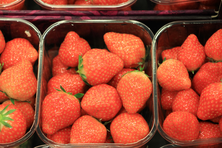 Fresh red strawberries arranged in baskets ready for sale at marketplace.