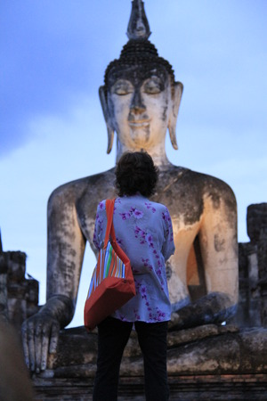 budda: The women is standing in front of the big buddha