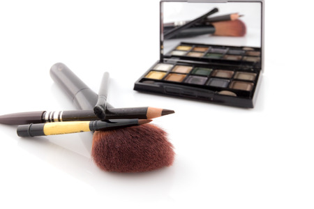 Cosmetic set - shadows for eyes, a mirror and a brush photo
