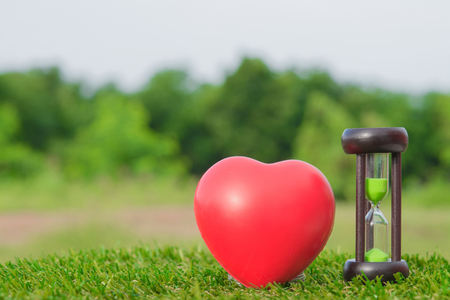 Red Heart Hourglass on natural background. Stock Photo
