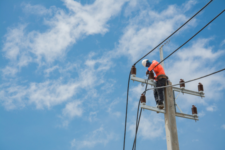 electricians repairing wire of the power line on electric power pole Stock Photo