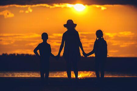 une silhouette familiale au coucher du soleil