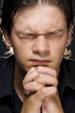 reverent: Closeup portrait of a young man praying to god