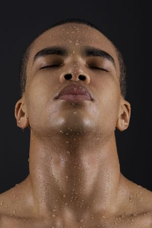 Drops of the water on face of a young man on black background.  photo
