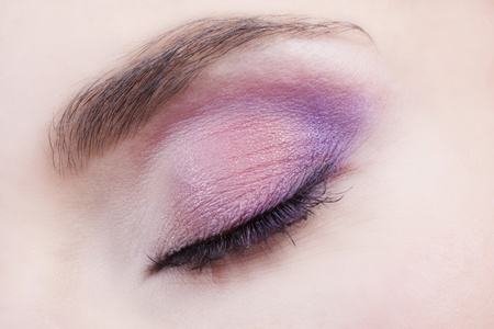 Woman beautiful eye with bright pink and violet makeup  photo