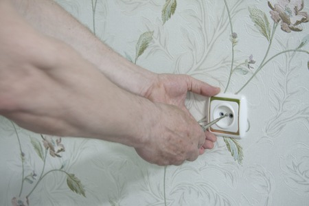 Interior repair. A professional electrician repairs socket on wall. 스톡 콘텐츠