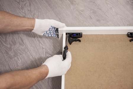 Repair and installation of furniture in the room. Male workers hands in white gloves
