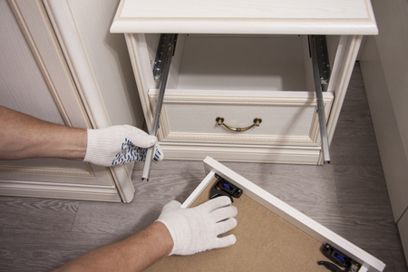 Repair and installation of furniture in the room. Male workers hands in white gloves Reklamní fotografie - 117498388