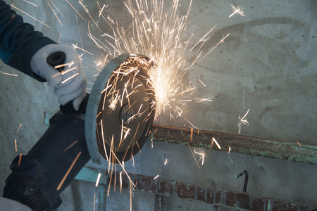 Repair work indoors. Angle Grinder Saws Metall. 스톡 콘텐츠