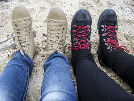 Female legs girlfriends on the beach in shoes. Gray and black sneakers with red laces in jeans. Sand by the sea. Lifestyle travel. Reklamní fotografie - 120357702