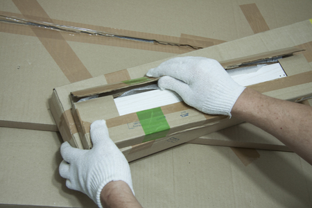 Male hands in white gloves with a knife unpack the box.