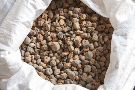 Natural mineral for construction. Expanded clay pebbles in a bag close-up.