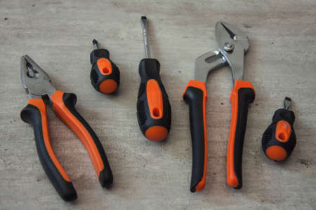 Construction and repair tools. Set on a wooden background. Metal screwdrivers and pliers with black and orange handles. Equipment for electrician, plumber and installer Banco de Imagens