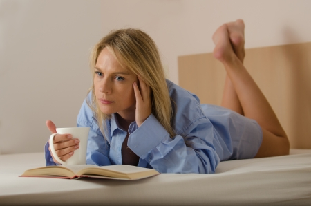 young beautiful woman is reading a book and drinking coffee photo