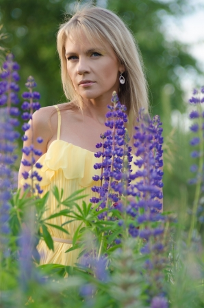 Young beautiful woman in the lupine field  Stock Photo