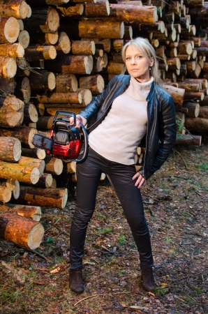 Young pretty woman with huge red chainsaw