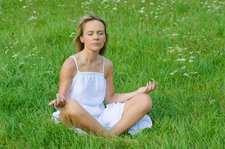young woman practicing yoga in nature photo