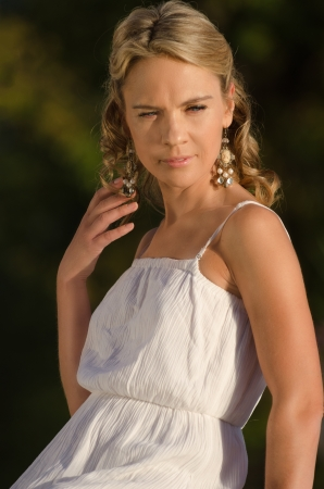 young pretty blonde with white dress outdoor