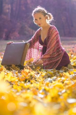 portmanteau: Autumn portrait of young pretty woman, with a vintage portmanteau