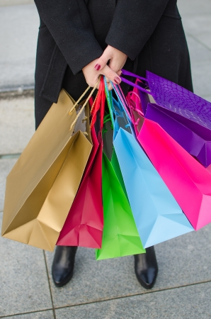 Parts of body of young woman with shopping bags photo