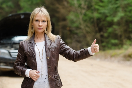 Young woman hitchhiking at broken car in the forest Stock Photo