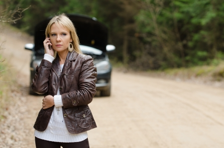 Young woman at broken car with mobile phone photo