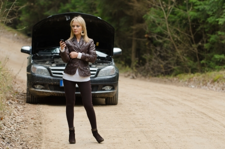 Young woman at broken car with mobile phone