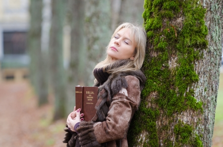 orison: Young woman with a Bible in the alley of park Stock Photo