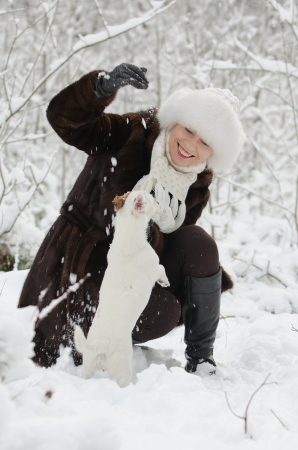 Young woman playing with  Jack Russell terrier in the snow photo