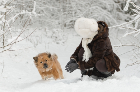 Young woman playing with dog in the snow photo