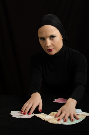 Woman in black with playing cards and money photo