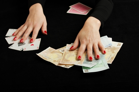 Hands of woman in black with playing cards and money
